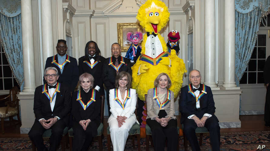 "Front row from left, 2019 Kennedy Center Honorees Michael Tilson Thomas, Linda Ronstadt, Sally Field, Joan Ganz Cooney, and Lloyd Morrisett, back row (l-r), Philip Bailey, Verdine White, Ralph Johnson, and characters from ""Sesame Street,"" Dec. 7, 2019."