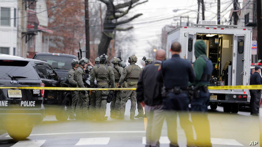 Police officers gather nearby the scene following reports of gunfire, Tuesday, Dec. 10, 2019, in Jersey City, N.J.  (AP Photo…