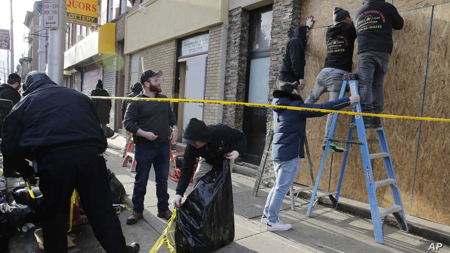 People board up the front of a kosher supermarket thats was the site of a gun battle in Jersey City, N.J., Wednesday, Dec. 11,…