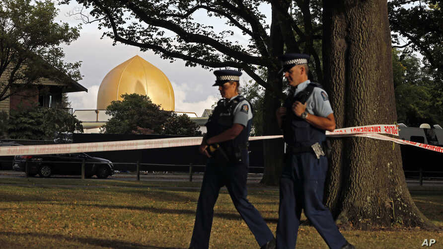 FILE - In this March 20, 2019, file photo, police officers patrol at a park outside the Al Noor mosque in Christchurch, New Zealand.