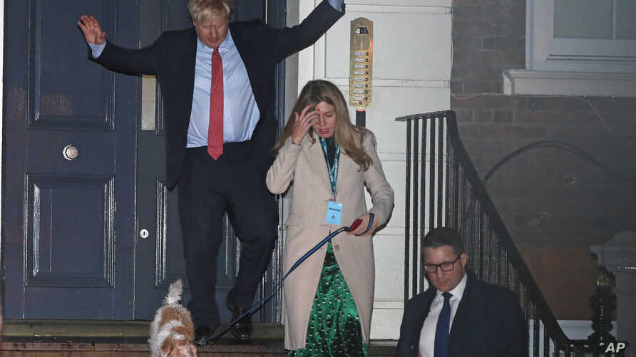 Britain's Prime Minister and Conservative Party leader Boris Johnson leaves Conservative Party headquarters with his partner Carrie Symonds and their dog Dilyn, in London, Dec. 13, 2019.