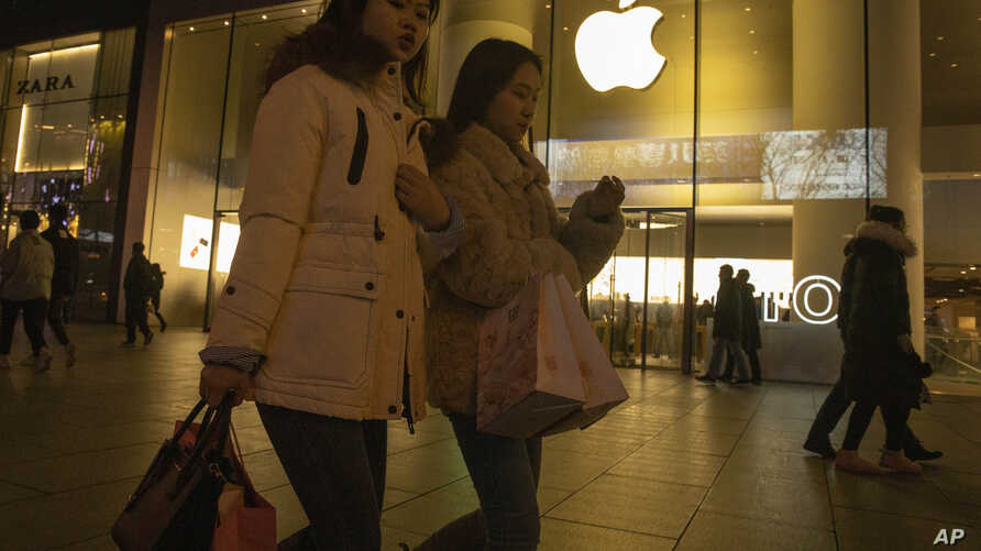 Shoppers walk past a store of US tech giant Apple in a retail district in Beijing, Dec. 13, 2019.