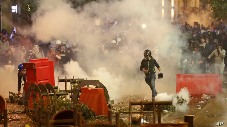 Anti-government protesters clash with the riot police, during a protest near the parliament square, in downtown Beirut, Lebanon…