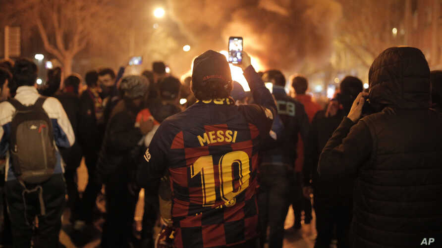 A man takes photos of fires that burn toward the end of a Catalan pro-independence protest outside the Camp Nou stadium in…