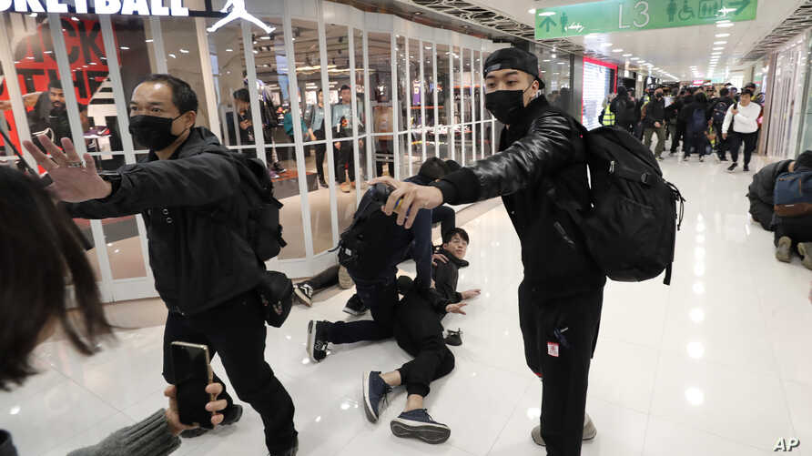 An undercover policeman points a can of pepper spray as others detain a protester during a demonstration at a shopping mall popular with traders from mainland China near the Chinese border in Hong Kong, Dec. 28, 2019.