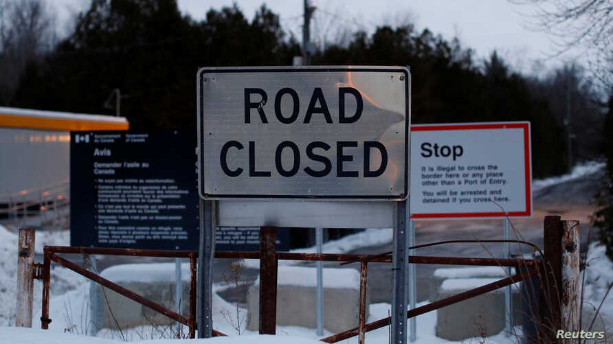 Signs are pictured at the US-Canada border as seen from Roxham Road in Champlain, New York, U.S., February 14, 2018. Picture…