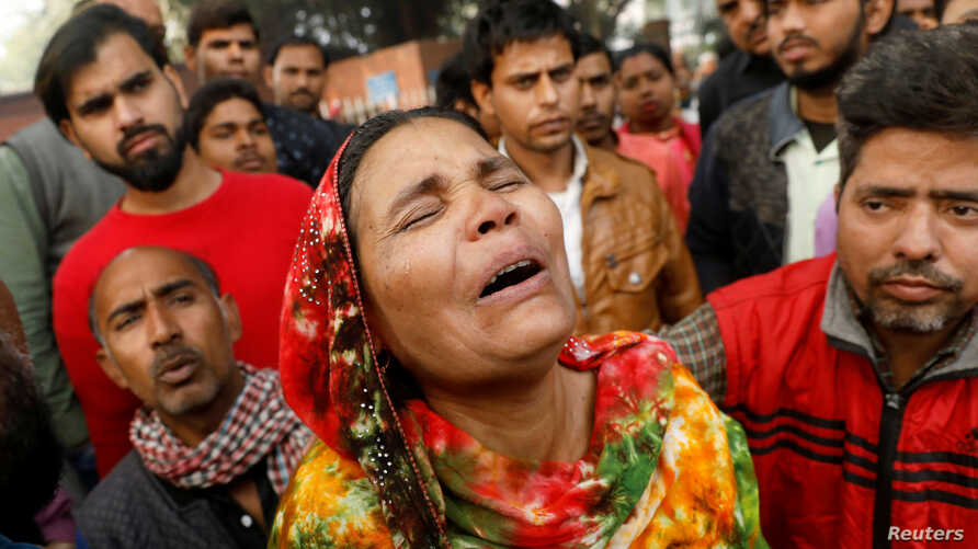 A relative of a victim of a fire that swept through a factory where laborers were sleeping, cries outside a hospital mortuary.
