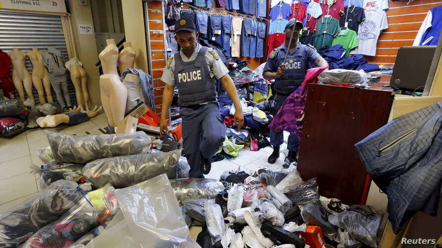 FILE - Police step over piles of suspected counterfeit clothing during a raid in Cape Town, South Africa, May 7, 2015.