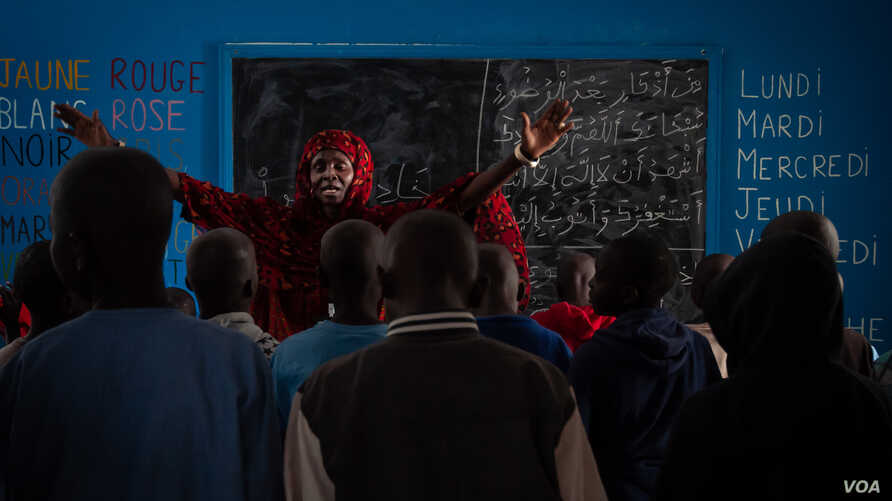 Talibés who were abused by their teachers learn the Koran from teacher Ya Seyda Fatoumata Diof at a shelter Dec. 12, 2019, in Dakar, Senegal. (Annika Hammerschlag/VOA)