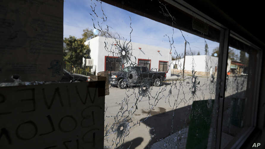 A shop's windows are riddled with bullet holes near City Hall after a gunbattle in Villa Union, Mexico, Dec. 2, 2019.