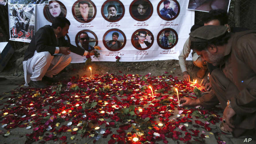 Afghan residents light candles to pay tribute to Afghan journalists killed in Monday's suicide attack in Kabul, May 3, 2018.