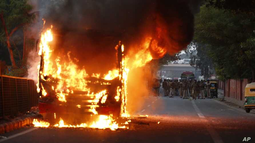 A passenger bus goes up in flames during a protest against the Citizenship Amendment Act in New Delhi, India, Dec. 15, 2019.