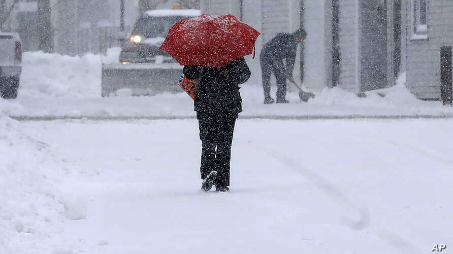 A pedestrian uses an umbrella while making their way down a snow-covered street, Dec. 3, 2019, in Norwood, Massachusetts.