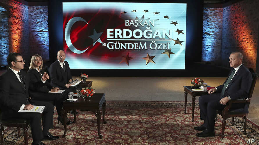 Turkey's President Recep Tayyip Erdogan, right, speaks during an interview with private A Haber and ATV television channels, in Istanbul, Turkey, Dec. 15, 2019.