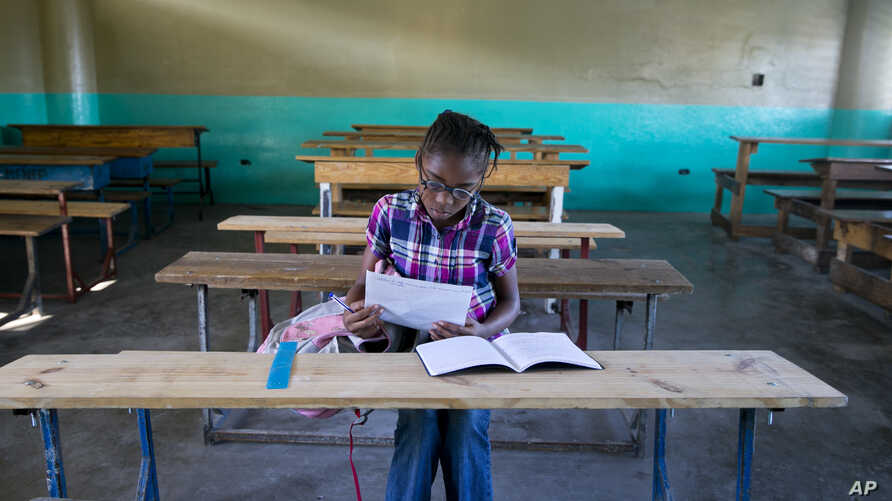 A lone student looks over papers as she waits for her teacher to arrive at the Lycée school, which reopened about a week earlier than other schools in Petion-Ville, Haiti, Nov. 28, 2019.