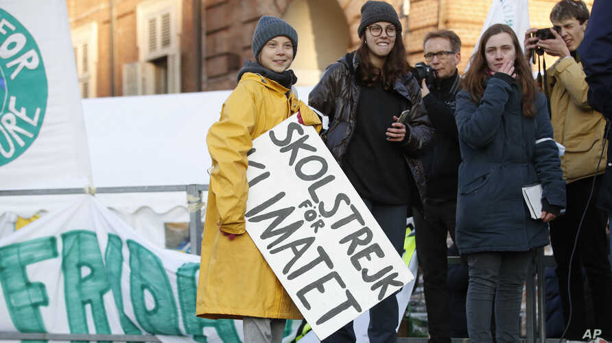 "Swedish environmental activist Greta Thunberg holds a sign with writing reading in Swedish ""School strike for the climate"" as…"