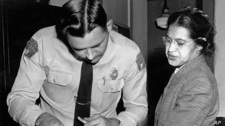 FILE - In this Feb. 22, 1956, photo, Rosa Parks is fingerprinted by police Lt. D.H. Lackey in Montgomery, Alabama, after refusing to give up her seat on a bus for a white passenger Dec. 1, 1955.