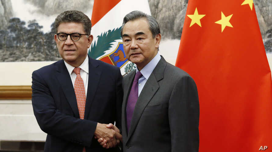 Peru's Foreign Minister Gustavo-Meza Cuadra, left, and Chinese Foreign Minister Wang Yi shake hands before a talks at the Diaoyutai state guesthouse in Beijing, China, Nov. 29, 2019.