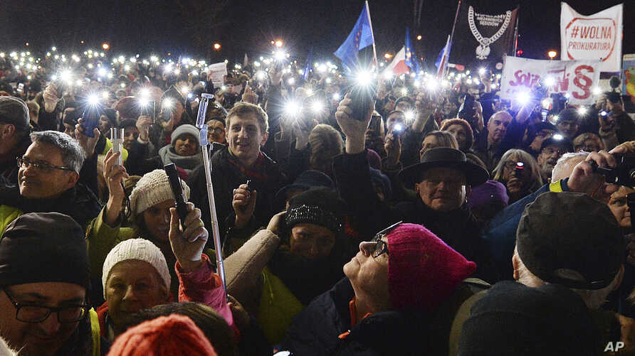 FILE - People take part in a street protest to show solidarity with judges facing increased political pressure from the country's right-wing government, in Warsaw, Poland, Dec. 1, 2019.