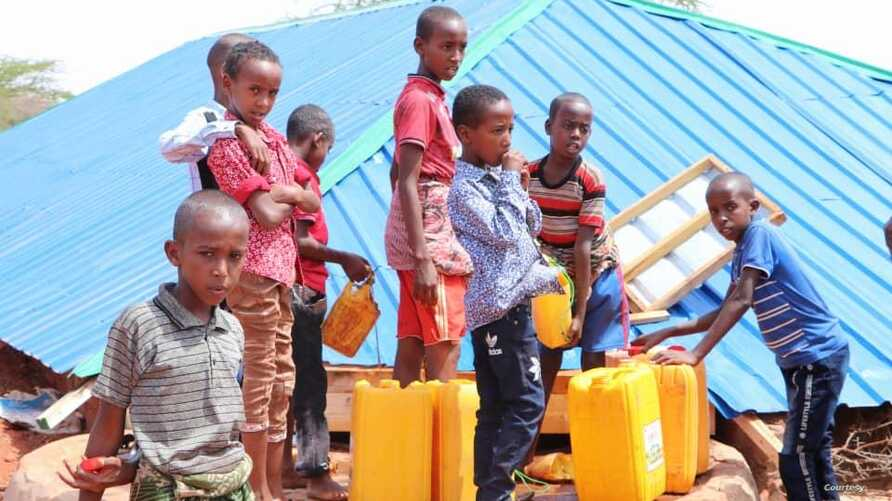 Children are filling their water containers at the makeshift Camp for Yemeni refugees near the Somali capital Mogadishu. (Courtesy of Muslim Aid)