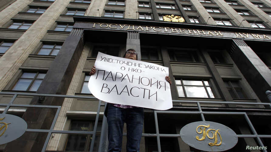 """FILE - A lone protester demonstrates against the original NGO foreign agent law, outside the Duma, Russia's lower house of parliament, in Moscow, Russia, July 6, 2012. The placard reads """"Tightening the NGO law speaks to the paranoia of authorities."""""""