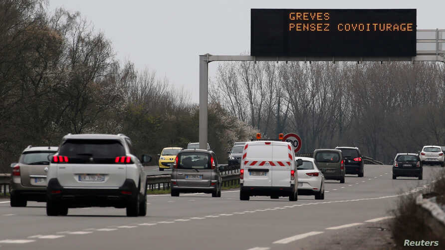 """FILE - Motorists drive on the Lille-Valenciennes highway as an illuminated road sign reads """"Strikes, think carpooling,"""" in Raismes, France, April 2, 2018."""