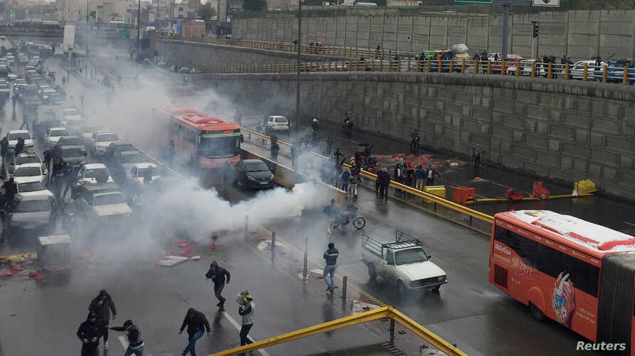 Riot police try to disperse protesters as they rally on a highway against increased fuel prices, in Tehran, Iran, Nov. 16, 2019.