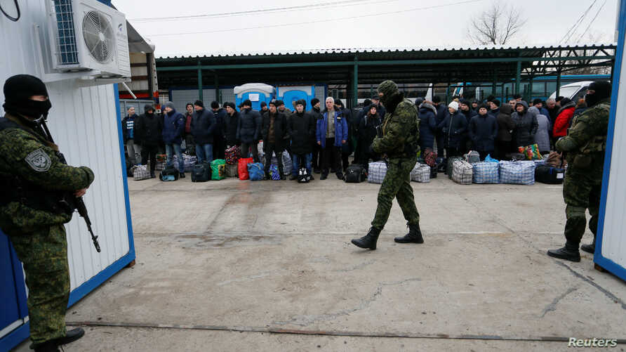 Ukrainian citizens are guarded by Russia-backed separatist fighters during a prisoner swap near Mayorsk, Donetsk region, Ukraine, Dec. 29, 2019.
