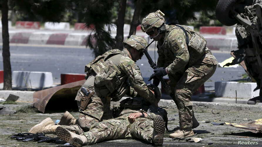 FILE - U.S. soldiers attend to a wounded soldier at the site of a blast in Kabul, Afghanistan, June 30, 2015.