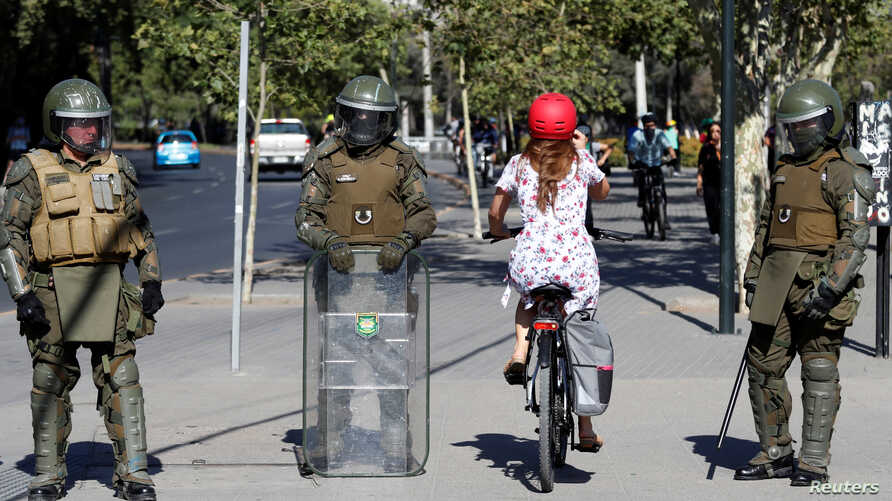 A woman rides a bicycle past police during a protest against Chile's government in Santiago, Chile, Dec. 4, 2019.