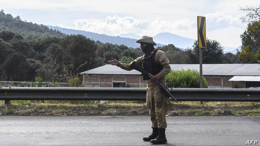 A member of the community police patrols the road in Cheran, Michoacan state, Mexico, on December 11, 2019. - Located on a…