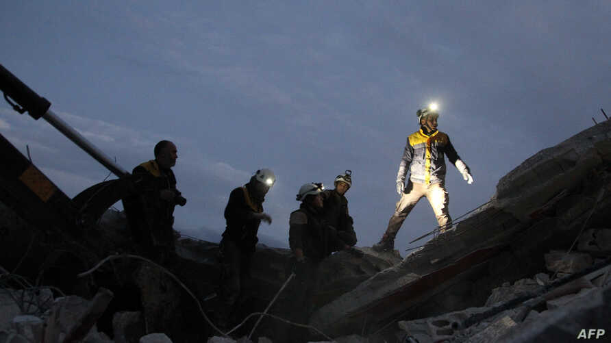 Members of the Syrian Civil Defence, also known as the White Helmets, search for survivors following an air-strike on the…
