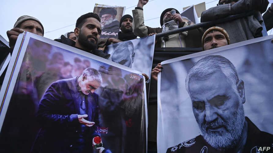 Protesters shout slogans against the United States and Israel as they hold posters with the image of top Iranian commander…