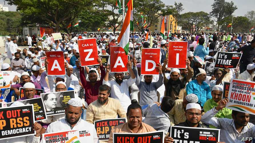 Muslim protesters hold placards and wave Indian flags during a protest rally against India's new citizenship law in Bangalore…