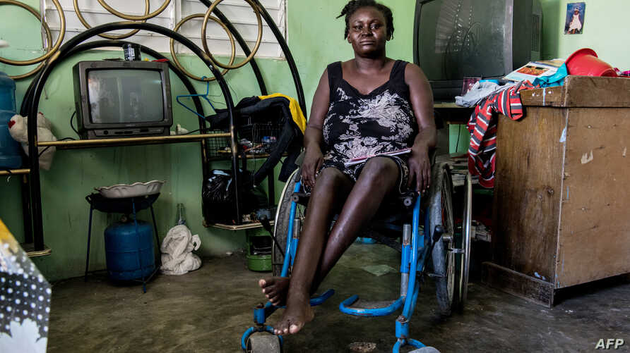 Herlande Mitile, 36 poses inside her house in Croix des Bouquets, 12.9kms (8 miles) northeast of Port-au-Prince
