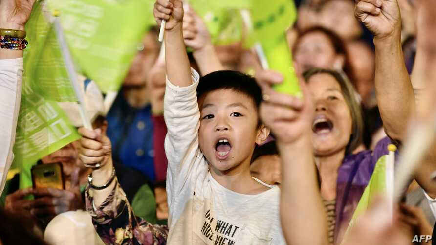 Supporters of Taiwan's President Tsai Ing-Wen, from the ruling Democratic Progressive Party (DPP), wave campaign flags dduring…