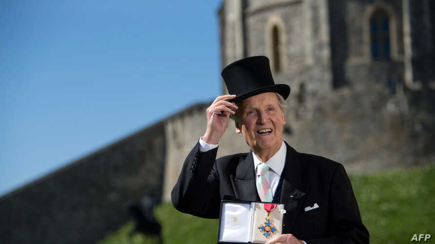 British radio and television presenter Nicholas Parsons poses with his Commander of the Order of the British Empire (CBE) medal…