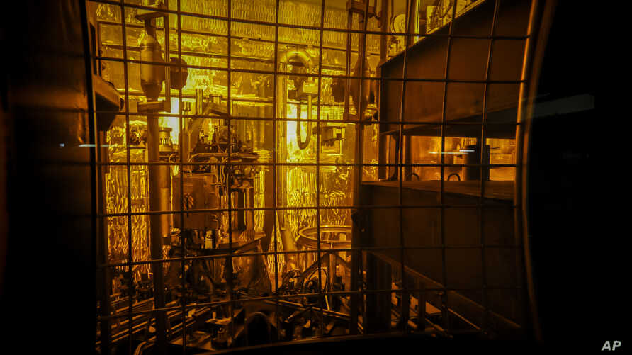 FILE - In this Nov. 20, 2013 file photo, seen through thick protective glass, shows the area where workers sand-blast the large…