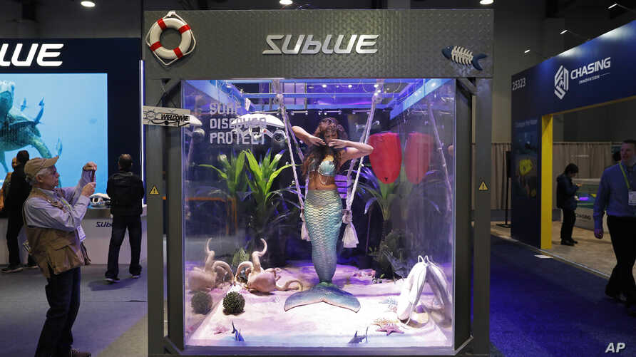 FILE- A woman dressed as a mermaid performs at the Sublue booth at CES International in Las Vegas.