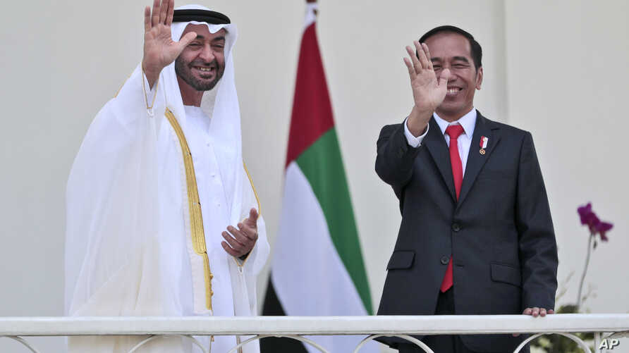 FILE - Abu Dhabi's Crown Prince Sheikh Mohammed bin Zayed Al Nahyan, left, and Indonesian President Joko Widodo wave at photographers during their meeting at the presidential palace in Bogor, Indonesia, July 24, 2019.