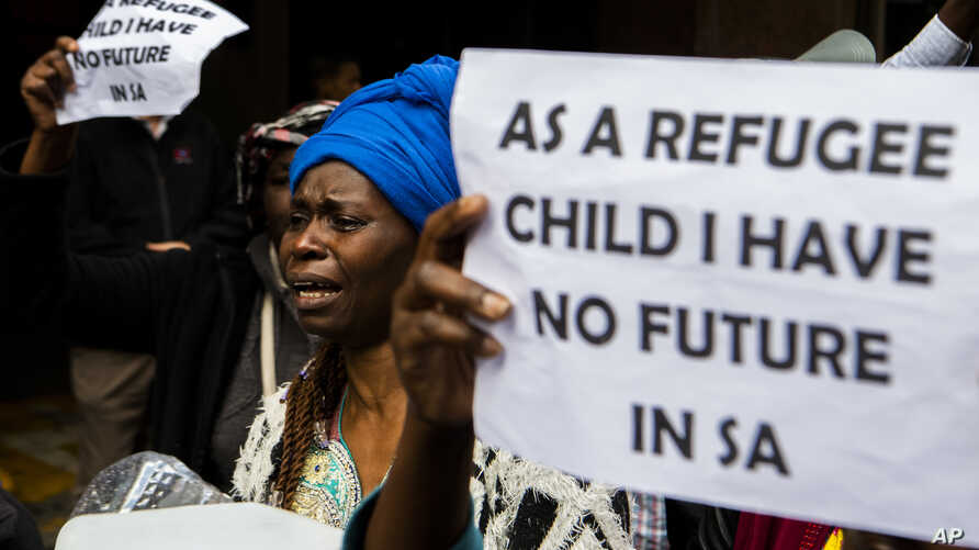 FILE - A woman protests with others outside the U.N. refugee agency offices in Cape Town, South Africa, Oct. 30, 2019.