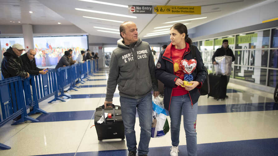 FILE - Mohammed Hafar, left, helps his daughter Jana with her luggage as they leave JFK Airport in New York.