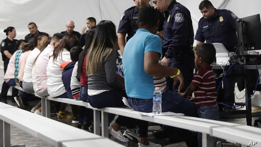 FILE - In this Sept. 17, 2019, file photo, migrants who are applying for asylum in the United States go through a processing…