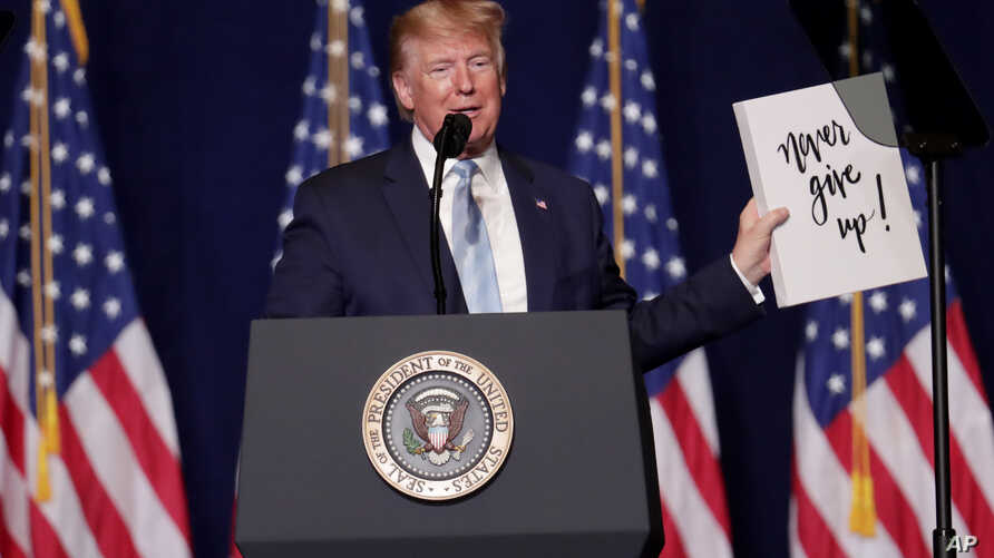President Donald Trump holds up a sign given to him by a supporter during a rally for evangelical supporters at the King Jesus International Ministry, Jan. 3, 2020, in Miami.