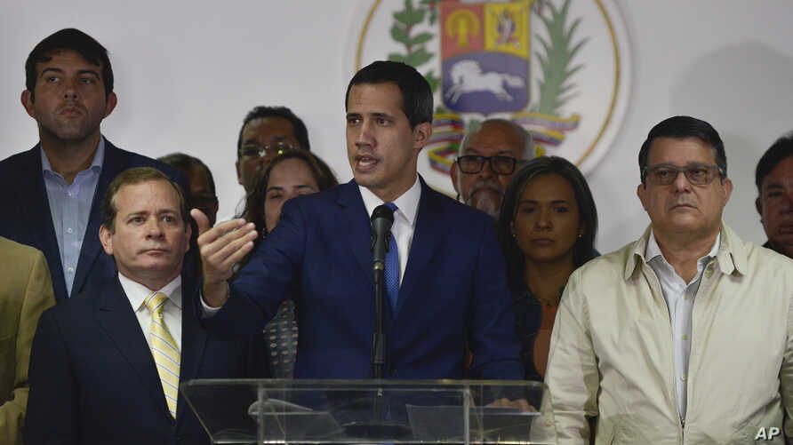 Opposition leader Juan Guaido, center, lawmaker Juan Pablo Guanipa, left, and lawmaker Carlos Eduardo Berrizbeitia, right, give…