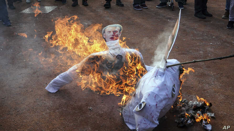 A picture of French President Emmanuel Macron burns during a demonstration in Lyon, central France, Jan. 9, 2020.