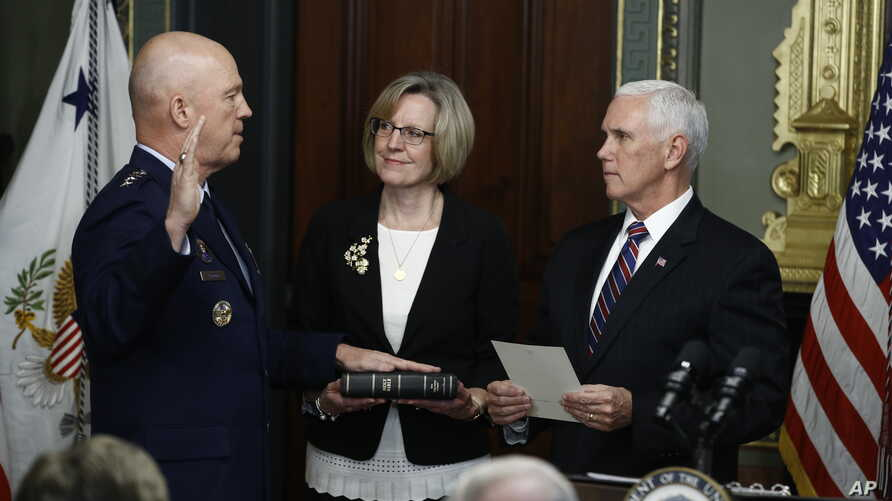 Vice President Mike Pence, right, swears in Air Force General John Raymond as Chief of Space Operations, in his Ceremonial Office in the White House complex, Jan. 14, 2020 in Washington, as his wife, Molly Raymond, looks on.