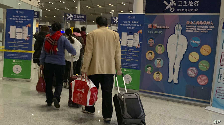 Travelers pass by a health checkpoint before entering immigration at the international airport in Beijing, Jan. 13, 2020.