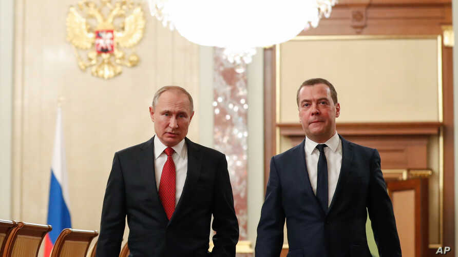 Russian President Vladimir Putin, left, and Russian Prime Minister Dmitry Medvedev walk prior to a cabinet meeting in Moscow.