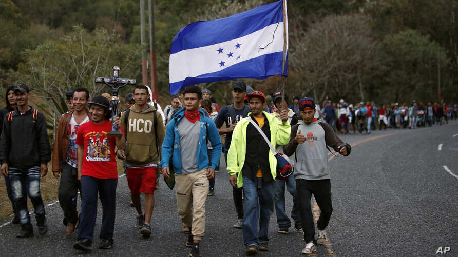 Honduran migrants walk north along a road in hopes of reaching the distant United States, one carrying a Honduran flag, as they…